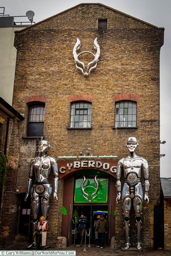 Two 6 metre tall metallic android figures flanking the entrance to Cyberdog fashion store, in one of the old industrial buildings in Camden Market.