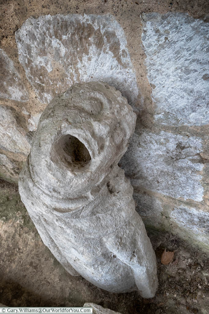 A piece of the stonework from the ruins of the Jumieges Abbey in Normandy depicting a tortured soul screaming out.