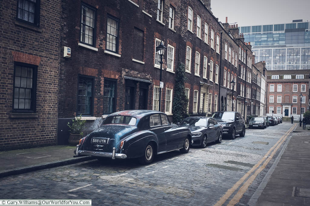 Elder Street, in the north of the Spitalfields district. A cobbled street of brick build Georgian terraced 3-storey houses. A classic 1950's Bentley is parked in a prime place.