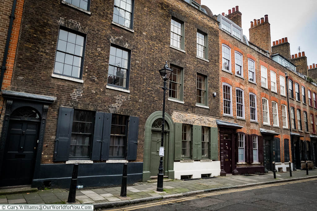 A view of the elegant Wilkes Street, Spitalfields, with its terraced 3 storey brick-built houses with shuttered windows, and cast iron bollards & lamp posts in a scene that hasn't changed since Dickensian times.