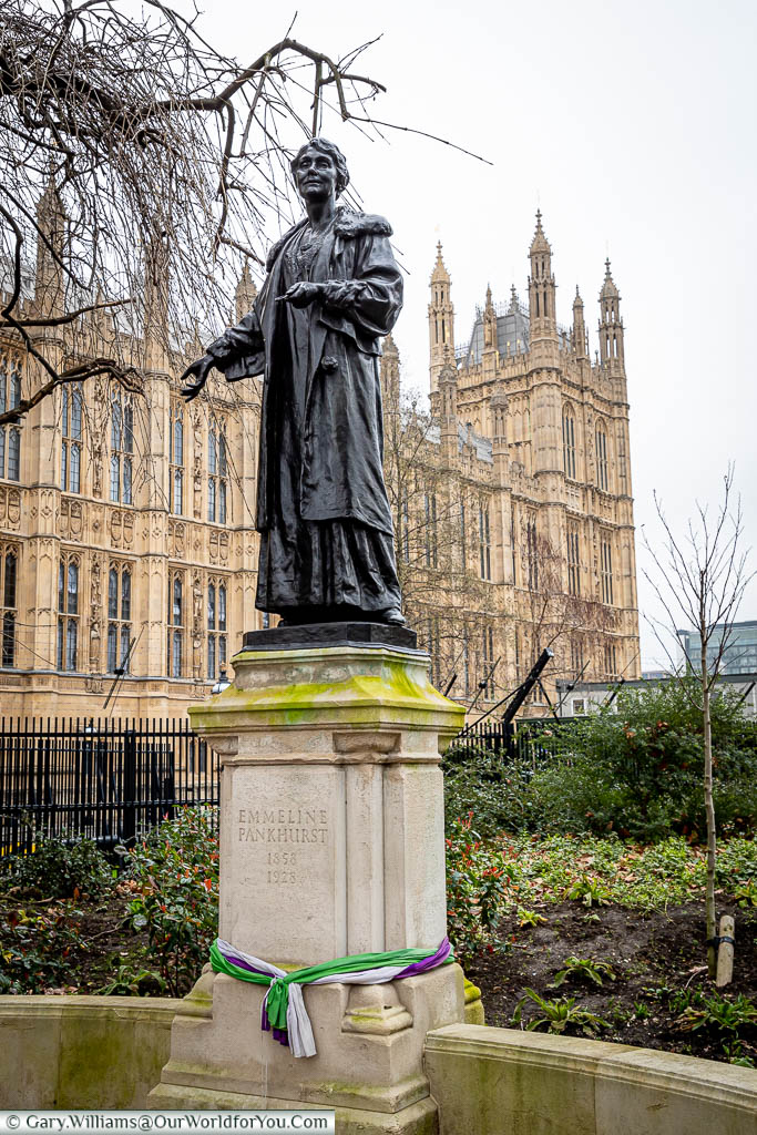 The bronze statue on a stone plinth to Emmeline Pankhurst, the suffragette, on the edge of Victoria Tower Gardens next to the Palace of Westminster.