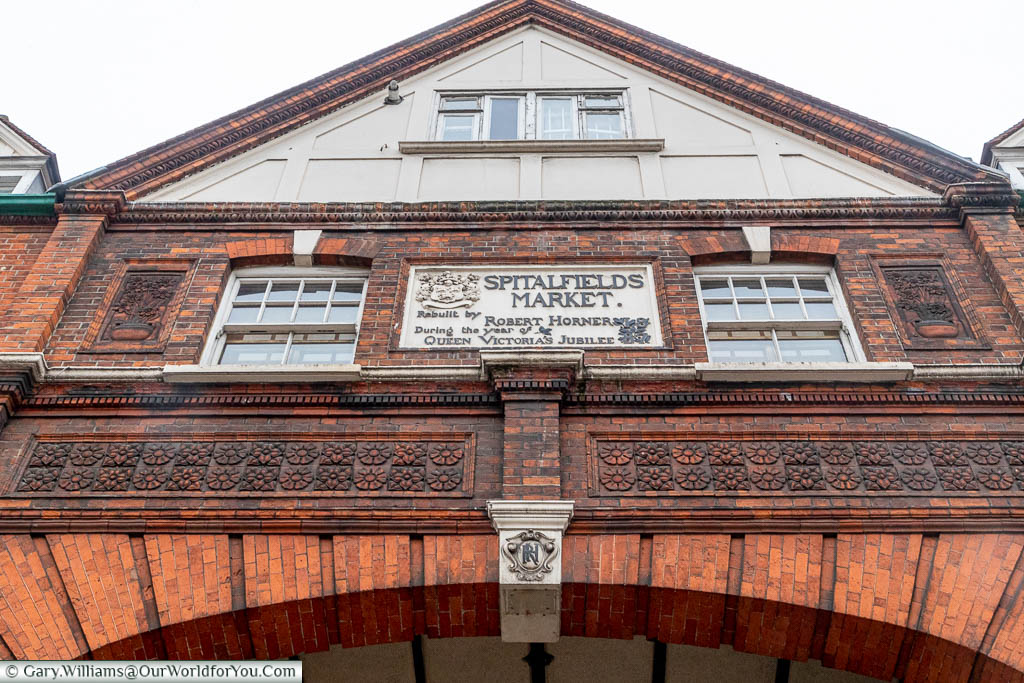 Looking up to the plaque above one of the entrances to the Spitalfields Market.  The plaque reads 'Spitalfields Market - Rebuilt by Robert Horner, during the year of Queen Victoria's Jubilee 1887'
