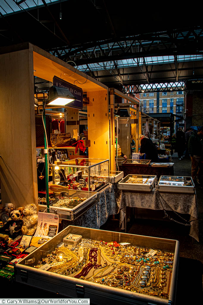 A stall selling all sorts of unique items, some in glass display cases, within the Spitalfields market.