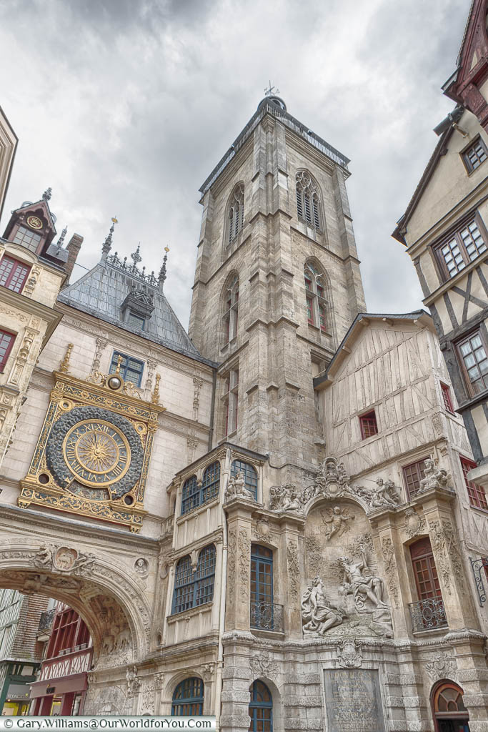 Rouen's famous Gros-Horloge.  An ornate, gold-trimmed,  clock mounted above an arch in one of the old town's thoroughfares next to a stone belfry.