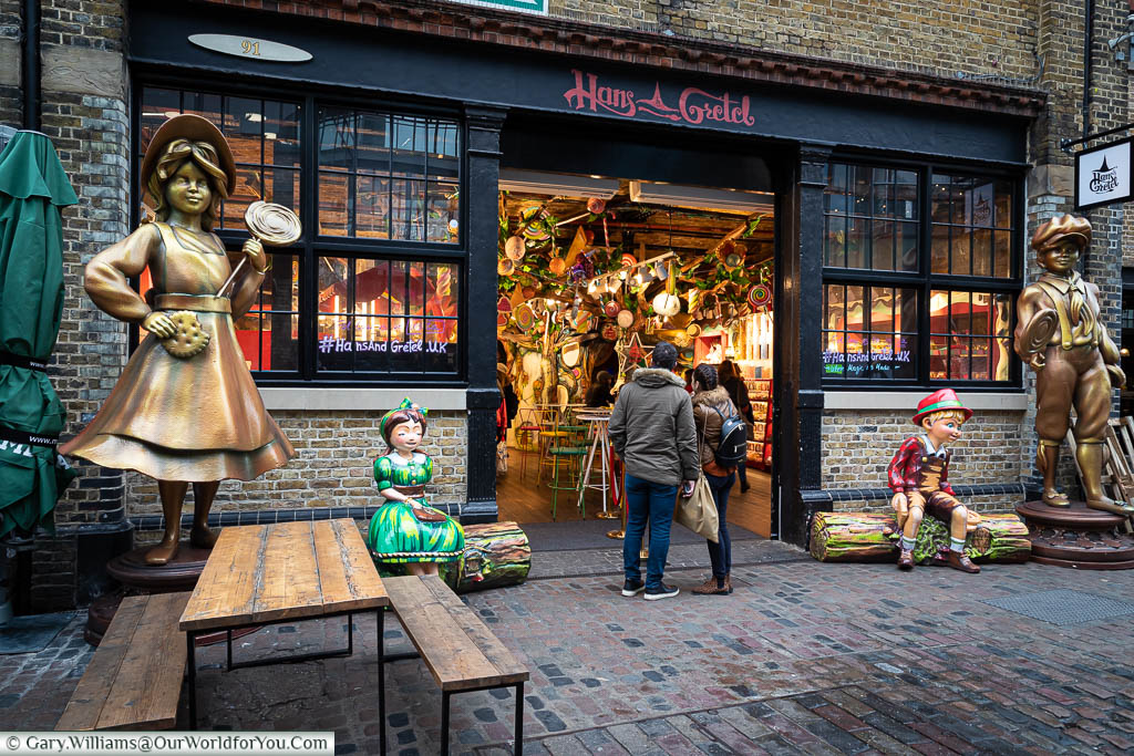 Playful statues of the titular characters frame the outside of the Hans & Gretel sweet store in the North Yard of Camden Market.