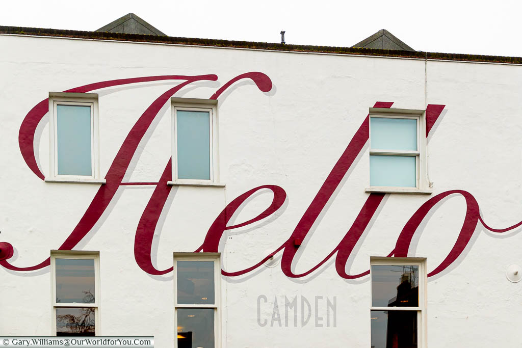 A 'Hello Camden' script in burgundy & grey painted on the front of a white building.