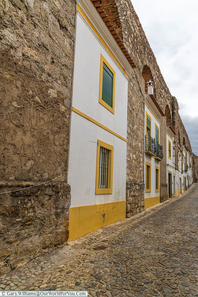 Homes in Évora, built between the arches of the aqueduct, each one in the traditional white and yellow of the region.