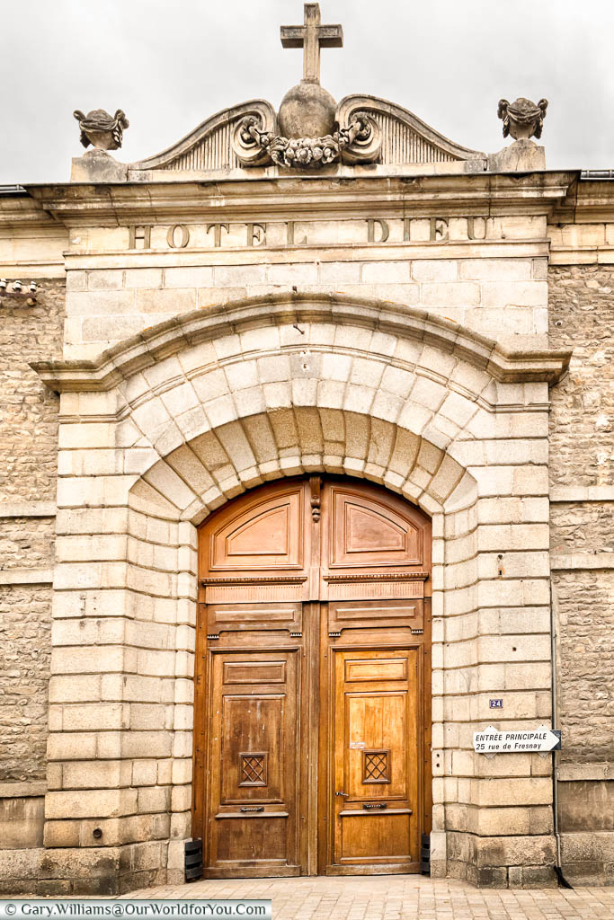 A large wooden door in a stone arch to the Hotel Dieu, which would have been a hospital for the poor & need of Alençon, France.