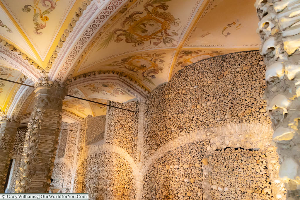 Inside the vaulted Chapel of Bones with a beautifully decorated ceiling and walls lined with a mixture of skulls & bones.