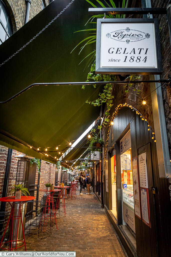 A look Italian Alley in Camden Market lined with tables & stools on one side and Italian treats on the other.  The first store is Gelati Pepino serving fine coffee and amazing gelato.