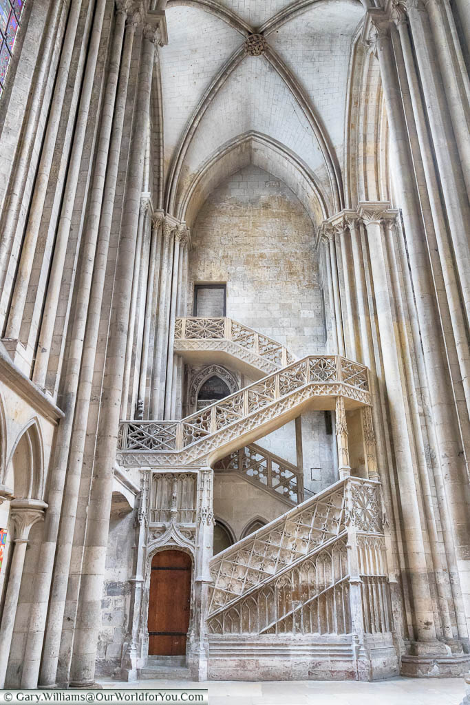 A portrait view of an elegant stone staircase, within Rouen Cathedral in Normandy, leading from a wooden door at ground level up two floors.  This ornate piece is known as the bookseller's staircase.