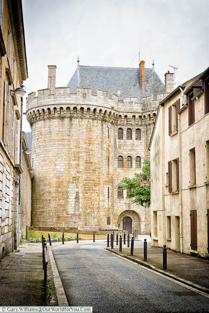The street view looking towords impressive stone towers of the entrance to 'Le Château des Ducs' in Alençon.