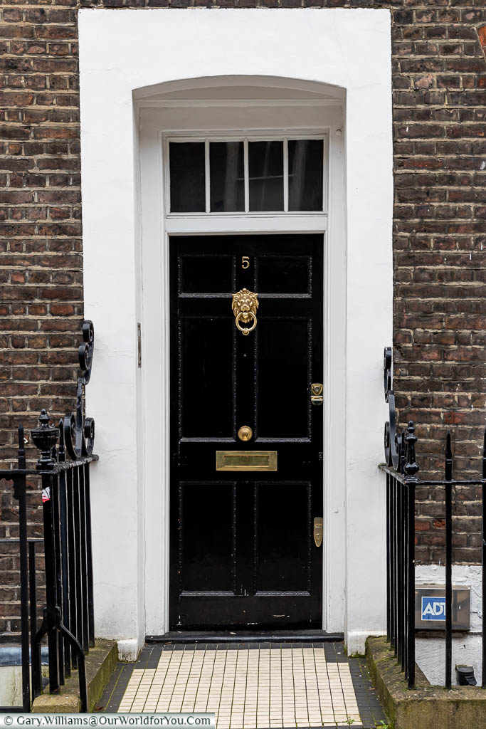 The front of number 5 Lord North Street, in Westminster, that was once home to British Prime Minister Harold Wilson.  A traditional black wooden door with a polished brass lion's head door knocker with a painted white surround.