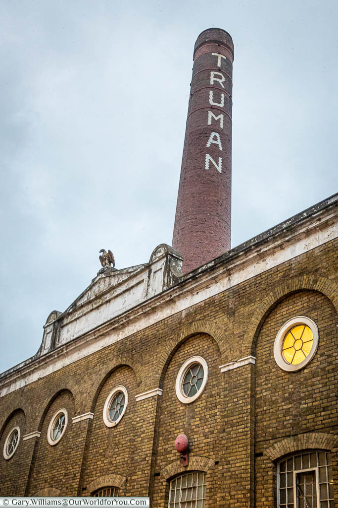 The brick building, and huge chimney stack, of the Truman's Brewery with its eagle statue.   The Chimney has the name of the brewery painted in large white letters down the tower.