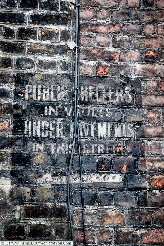 The stencilled sign on brickwork indicating the prence of an underground public air raid shelter in Westminster.