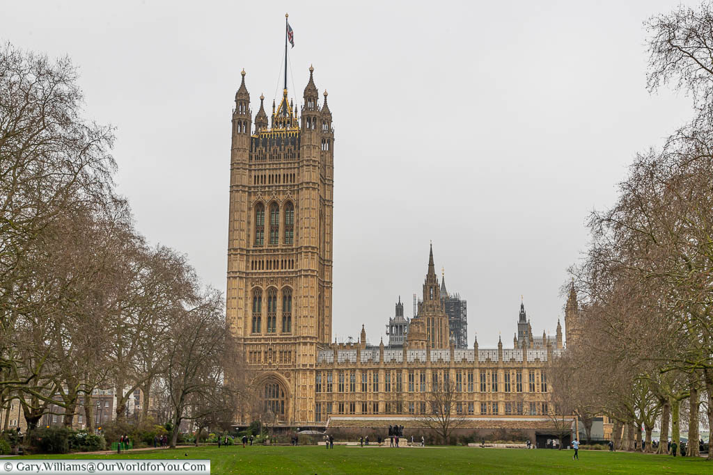 The Palace of Westminster, from Victoria Tower Gardens, with a Union Flag flying over the Victoria Tower.