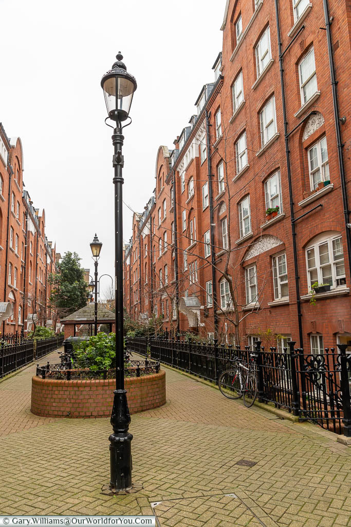 A courtyard between two apartment blocks with ornate, cast-iron, streetlamps in Regency Street, Westminster