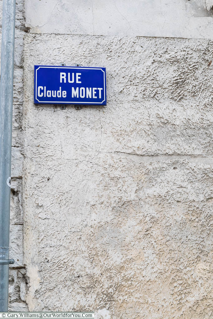 A traditional french street sign of white text on a blue enamel background for the Rue Claude Monet in Giverny