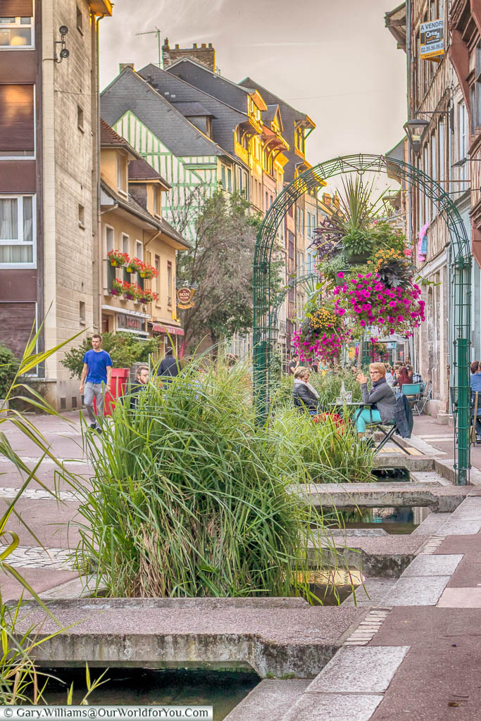 A  stream flowing along a restaurant-lined street in Rouen, Normandy
