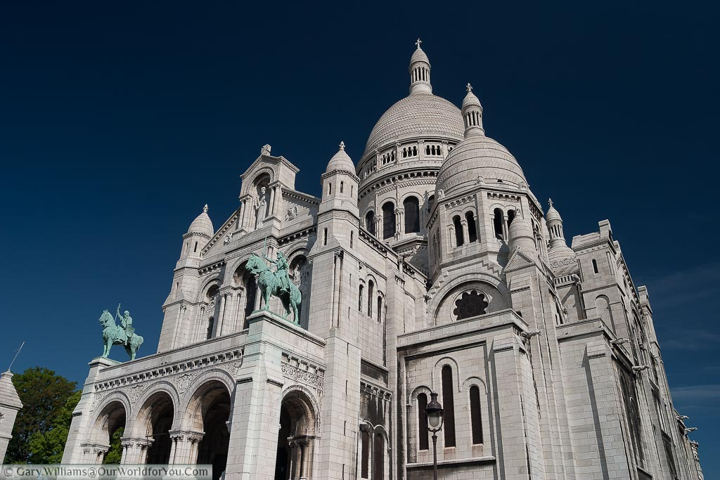 The white stone of the Sacré-Cœur Basilica in Paris set against a deep blue sky.