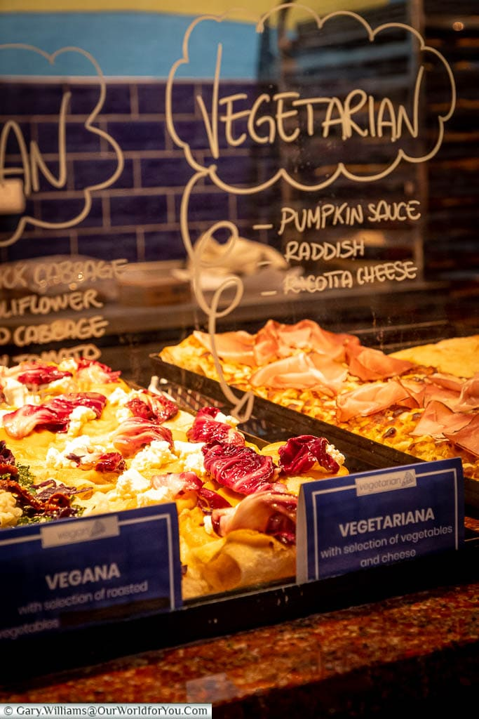 A selection of delicious-looking pizza slices with a variety of topping in Italian Alley in Camden Market.