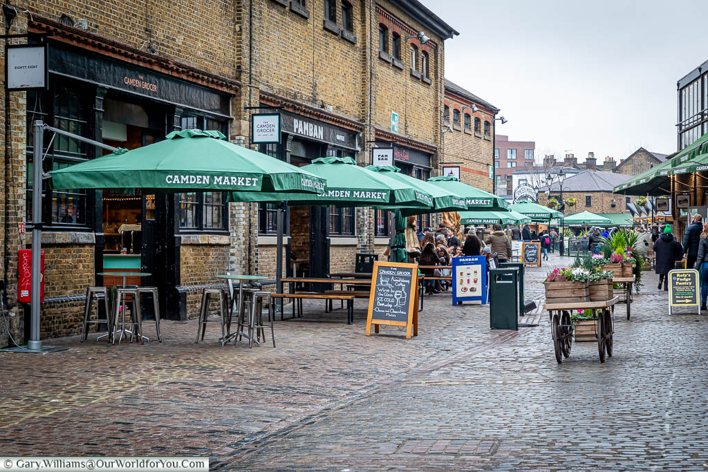 The cobbled courtyard of the North Yard of Camden Market, home to artisan food stores with parasol covered benches outside.