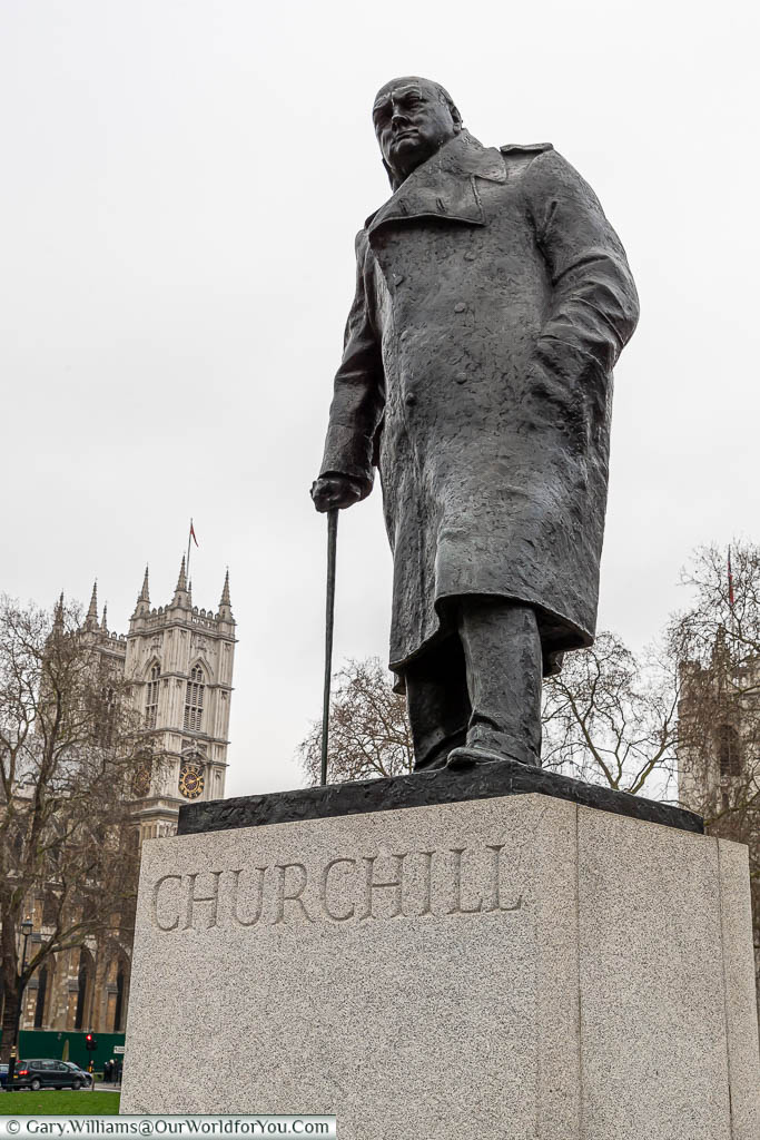 The bronze statue of Sir Winston Churchill in his later years wearing a heavy overcoat and using a walking stick, with the towers of Westminster Abbey in the background.