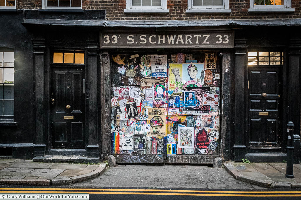 The entrance to 33a Fournier St in East London un the signage for S.Schwartz.  The wide gateway used to be a diary but has now become a street art installation featuring posters of work commentating on social issues.