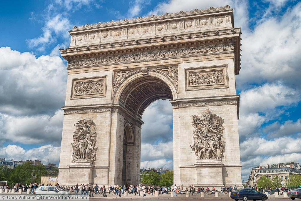 A close-up shot of the Arc de Triomphe in the centre of Paris's infamous roadabout taken on a bright day with bright white clouds scattered across a blue sky.