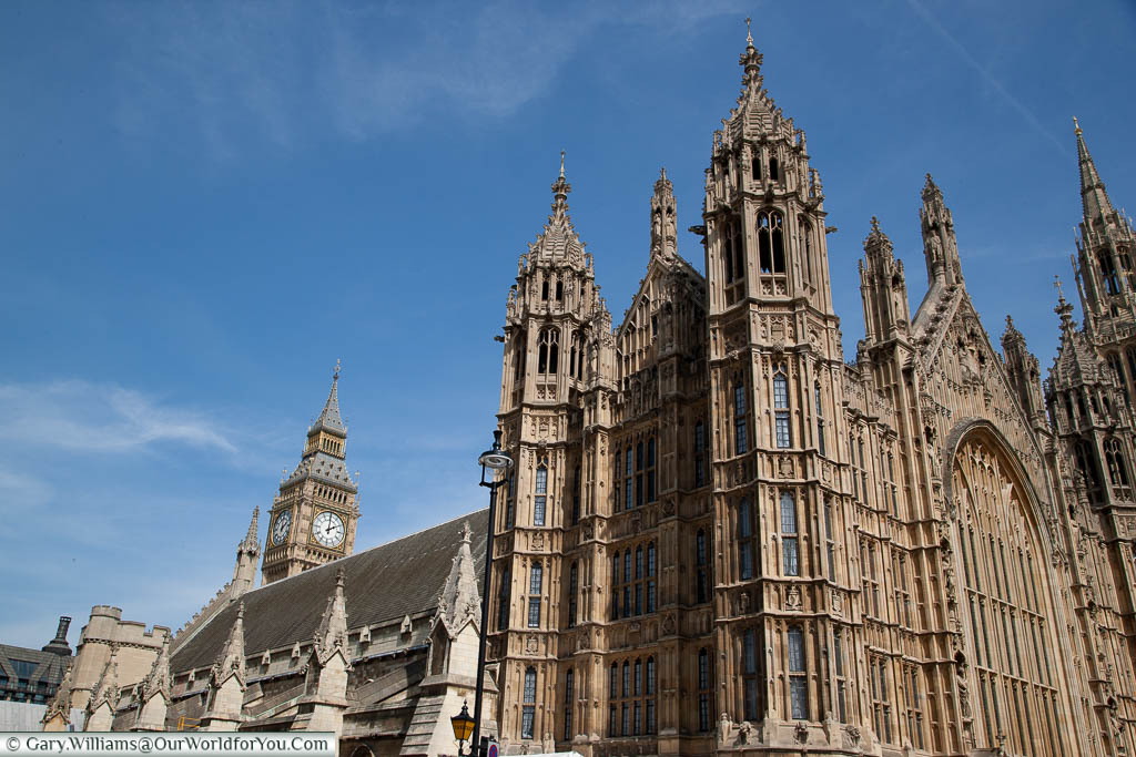 A close-up of the Palace of Westminster from the old court yard focusing on the neogothic detail.  In the background, you can see the top of the tower that houses 'Big Ben'