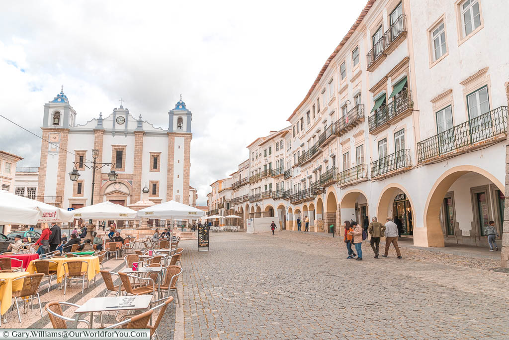 A street scene of the Praça do Giraldo in central Évora.  Tables and chairs lead the way to the Church of Saint Antão.