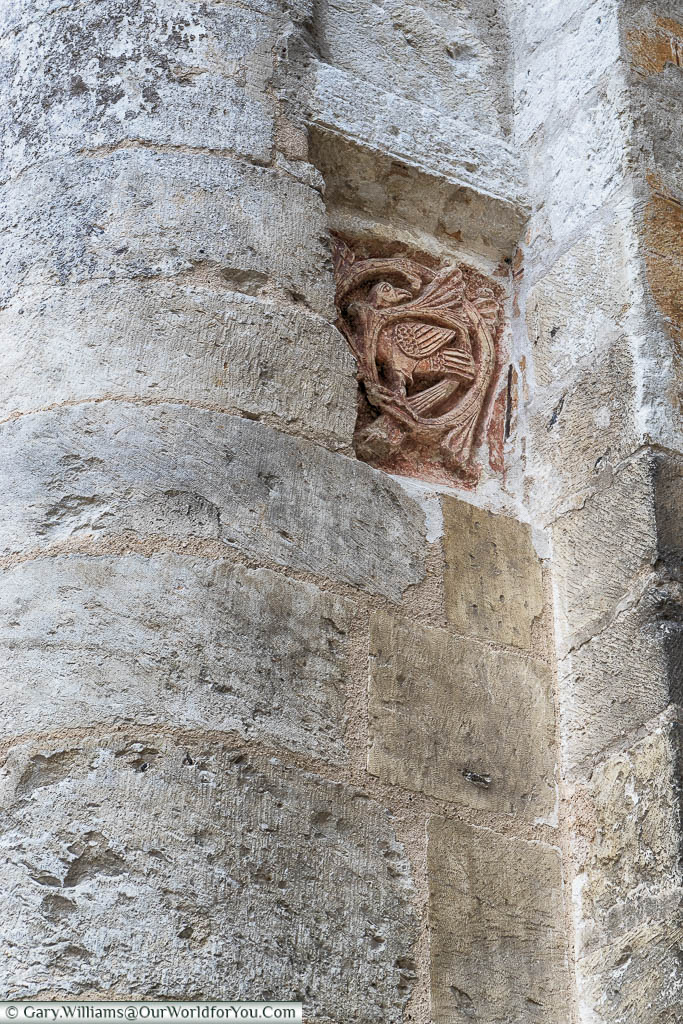 A tiny detail in the stonework of the Jumieges Abbey is a reddish tile of a Romanesque ochre bird which stands out against the white stone.