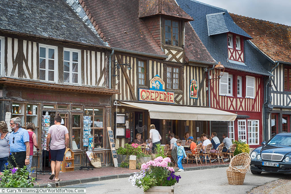 A creperie set in a row of half-timbered buildings next to the market square in Beuvron-en-Auge, Normandy.