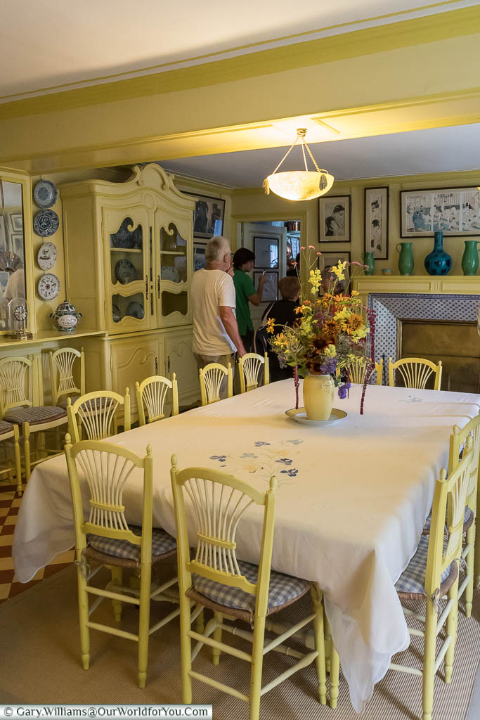 The dining area in Claude Monet's home with a simple table and chairs in a pale yellow colour.