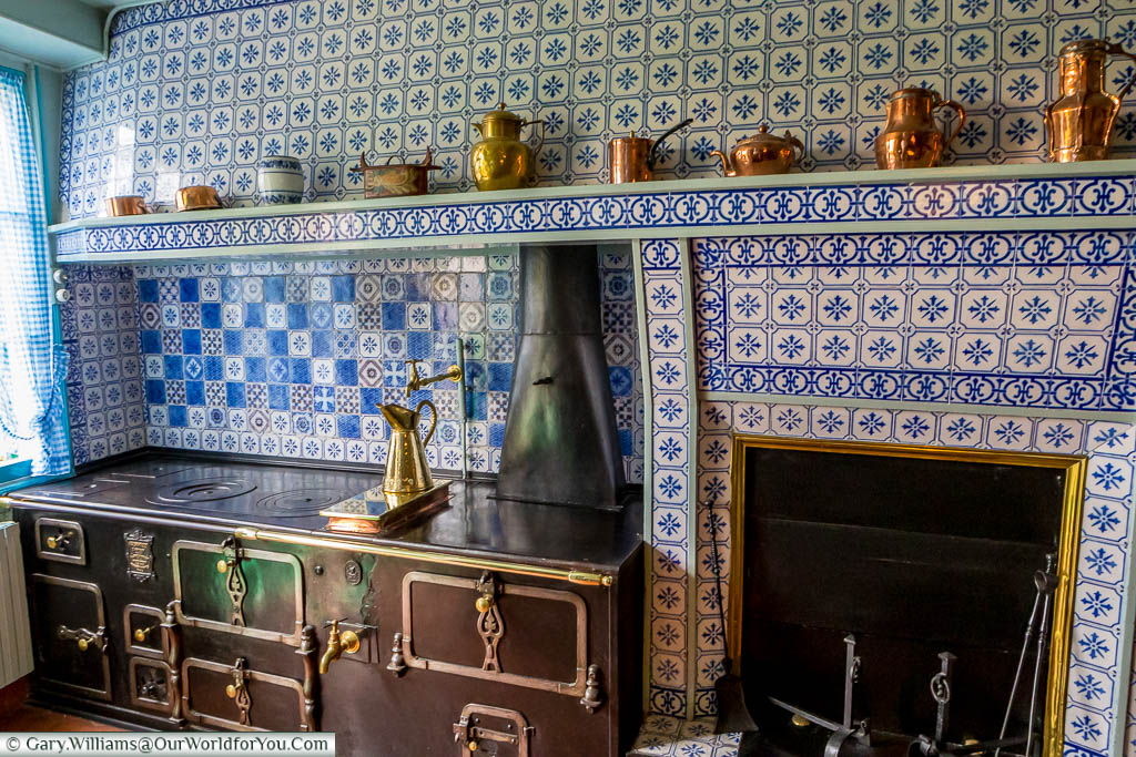 The traditional range cooker in the blue and white tiled kitchen of Claude Monet's home.