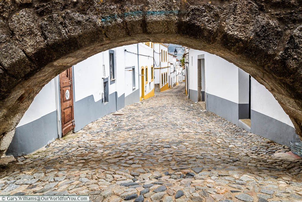 Peering through one of the arches of the Agua de Prata aqueduct to a cobbled white-washed lane of Évora.