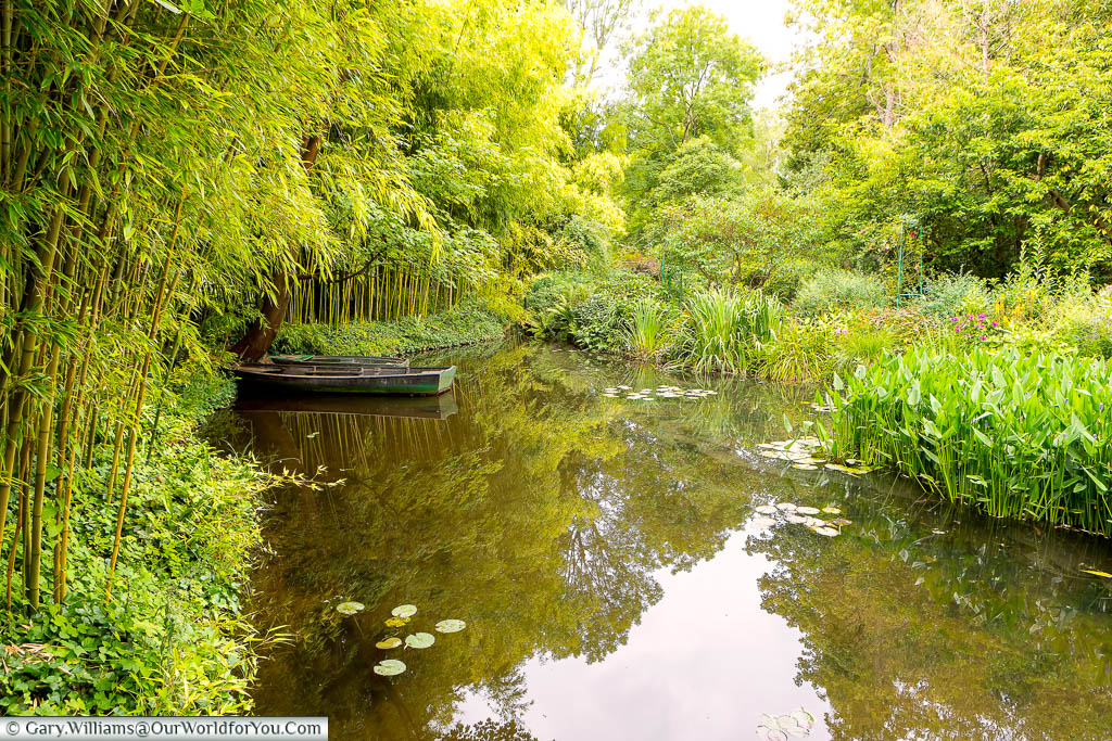 A small rowing boat sitting on the shoreline of one of the ponds in Claude Monet's gardens in Giverny, Normandy