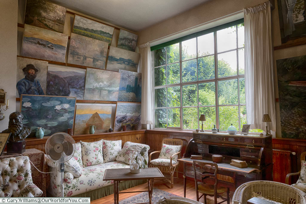 A collection of works adorn the salon in Claude Monet's home alongside a bureau with a view onto his gardens in Giverny.