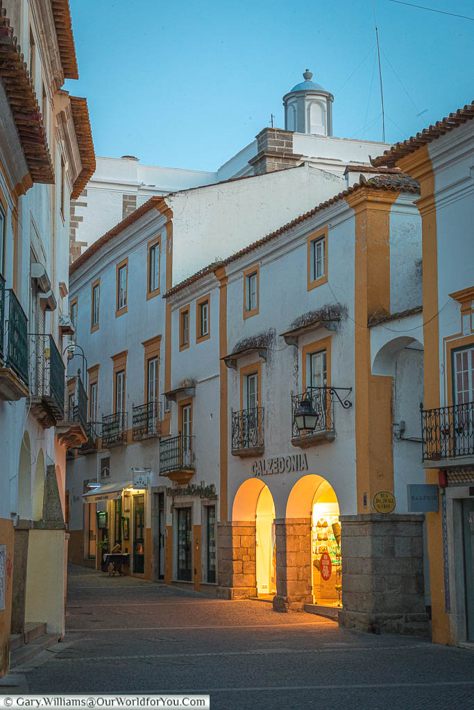 The lights of a gift store reflect onto a quiet lane in Évora as it meanders through the town.