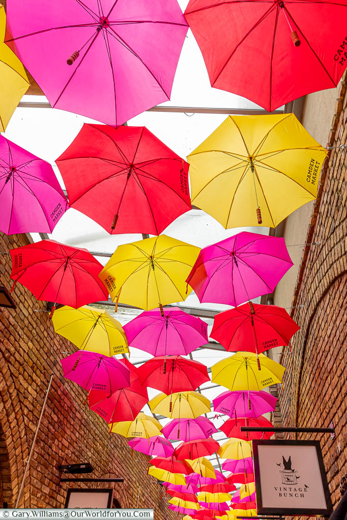 A mixture of pink, yellow & red opened umbrellas provide a canopy between the stores in one lane in Camden Market.