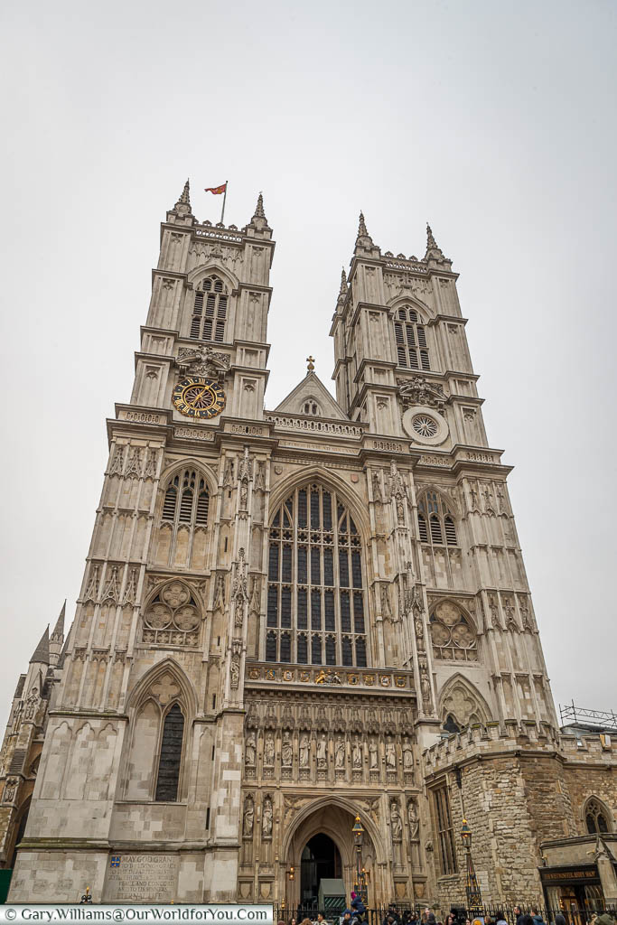 The facade of Westminster Abbey dominated by it's two white towers and large stained glass window.