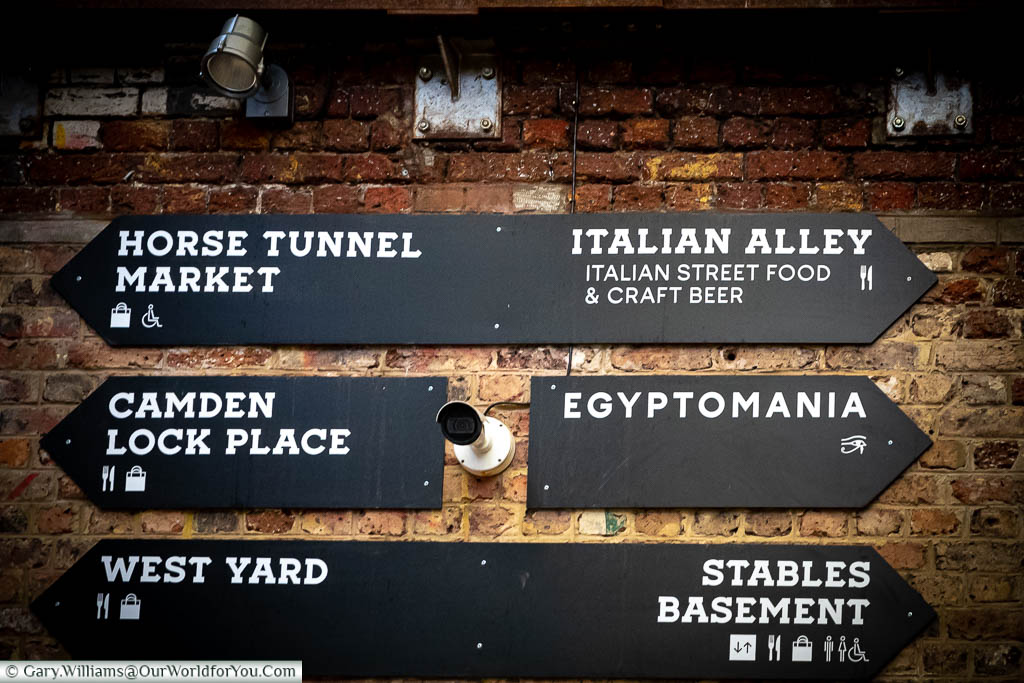 Black signs, with a white font, on a brick wall in Camden Market pointing out the key areas, including Horse Tunnel Market, Camden Lock Place, West Yard, Italian Alley, Egyptomania & the Stables Basement.