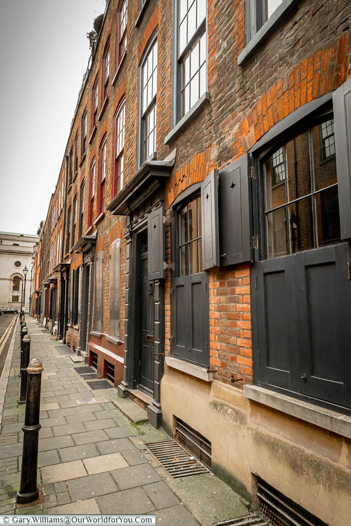 Looking along Wilkes Street, Spitalfields, a row of terraced 3 storey brick-built houses with their uniform black shuttered windows, and the pavement lined with cast iron bollards.