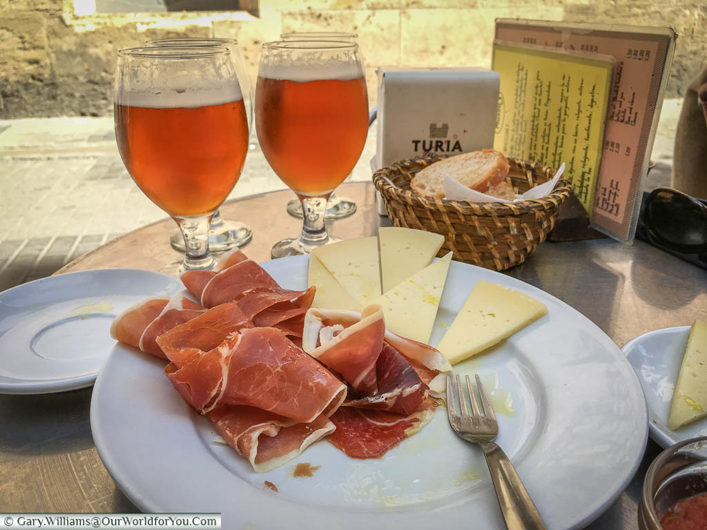 A plate of ham and cheese with a couple of beers at a table outside a restaurant in Valencia, Spain