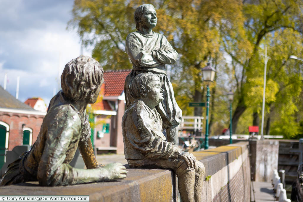 A collection of three bronze statues of boys on the harbour wall in Hoorn, Holland.