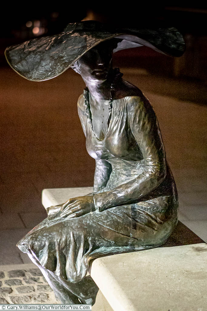 A brass statue of a lady seated on a stone bench with a broad-rimmed hat known as La Dame au Chapeau in Troyes, France