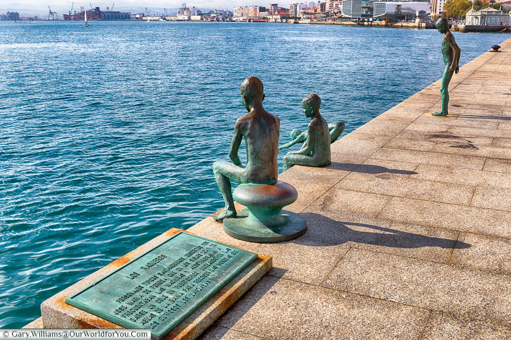 A plaque next to four bronze statues depicting young boys diving into Santander's natural harbour.
