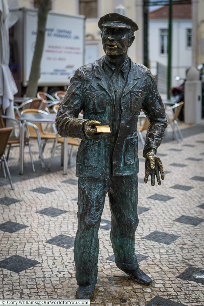 A bronze statue to a lottery ticket seller, complete with peaked hat, in a square in Lisbon.  The extended ticket in his hand has been buffed clean by those touching it for luck.