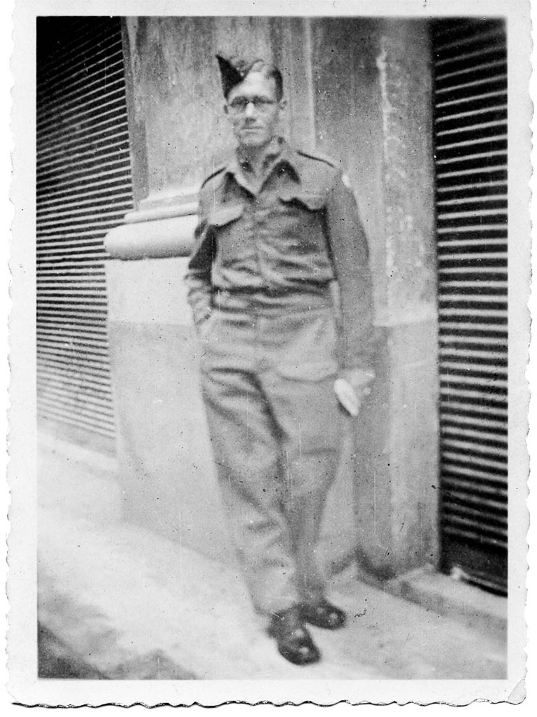 A black and white picture of Pop posing in his uniform in the street somewhere