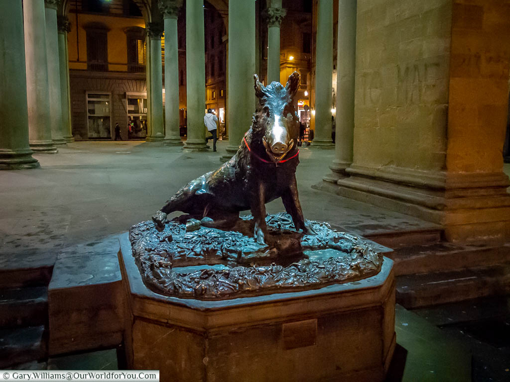 A bronze statue of a  wild boar in a seated postition at the edge of a market square in Florence. Its snout buffed by the number of people that have touched it for luck.